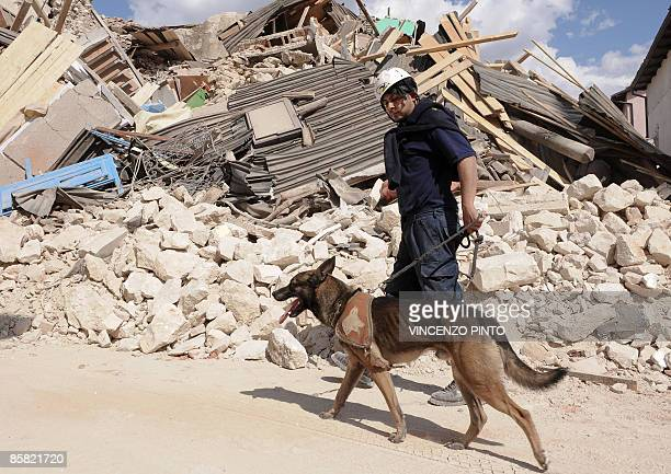 Rescuer walks with his dog on April 6, 2009 past a collapsed house in Onna, a small town some 10 kilometers from L'Aquila, epicentre of an earthquake...