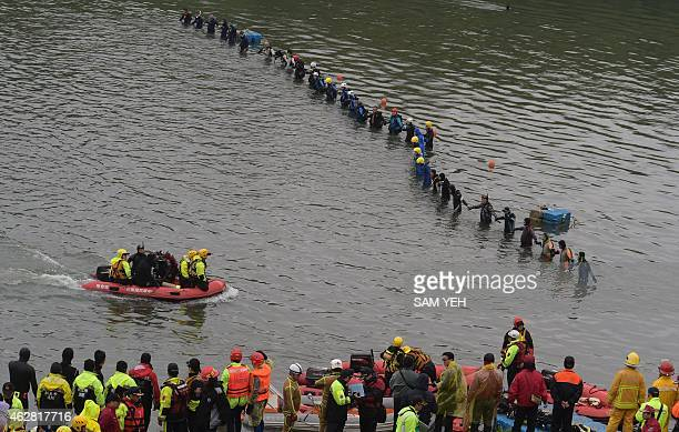 Rescuers and divers search for missing passengers at the crash site of the Transasia ATR 72-600 turboprop plane in the Keelung river in New Taipei...