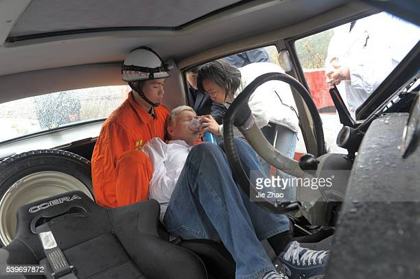 Rescuers and doctors move Pierreone of the members of a French old car tourist party out of his crashed car to hospital on 212 provincial highway...