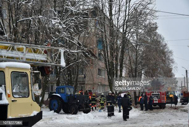 Rescuers and firefighters look at a partially destroyed fivestorey building on the site of a gas explosion in the town of Fastiv on December 14 2018...