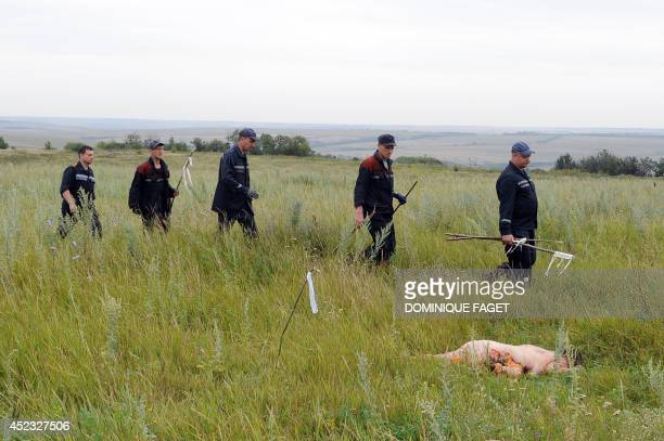 Rescuers and firefighters walk near the body of a passenger on July 18 2014 on the site of the crash of a Malaysian airliner carrying 298 people from...
