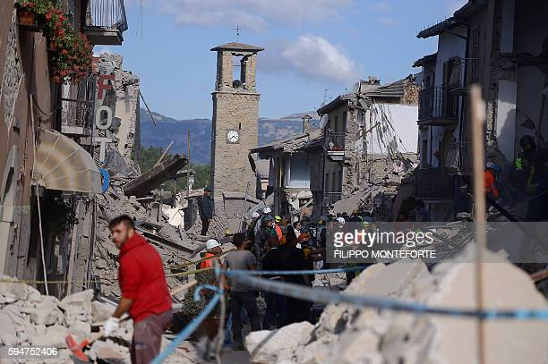 Rescuers and firemen inspect the rubble of buildings in Amatrice on August 24 2016 after a powerful earthquake rocked central Italy The earthquake...