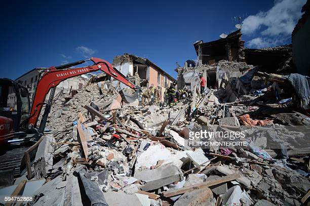 TOPSHOT Rescuers and firemen inspect the rubble of buildings in Amatrice on August 24 2016 after a powerful earthquake rocked central Italy The...