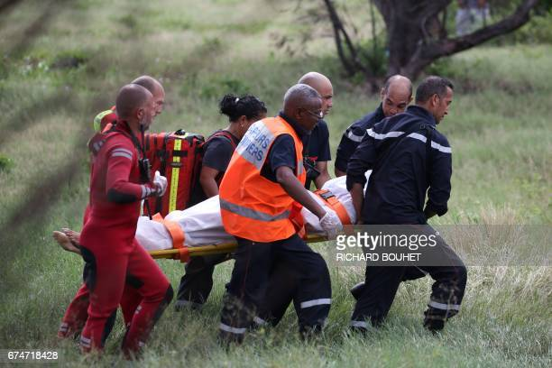 Rescuers and gendarmes carry on a stretcher the body of young bodyboarder who died following an attack by a shark on April 29 2017 in SaintLeu on the...