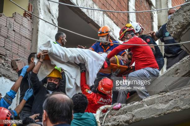 Rescuers and local volunteers carry a wounded victim on a stretcher from a collapsed building after a powerful earthquake struck Turkey's western...