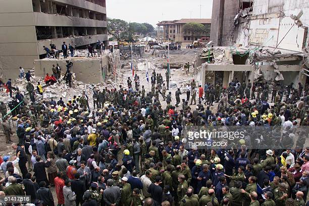 Rescuers and officials stand at the site in front of US embassy 12 August in Nairobi after a ceremony for those killed in the 07 August bomb attack...