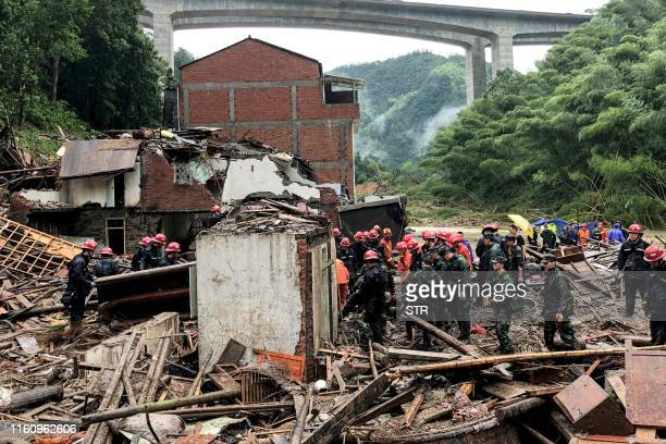 Rescuers and paramilitary police officers search in the rubble of damaged buildings after torrential rain caused by Typhoon Lekima at Yongjia in...