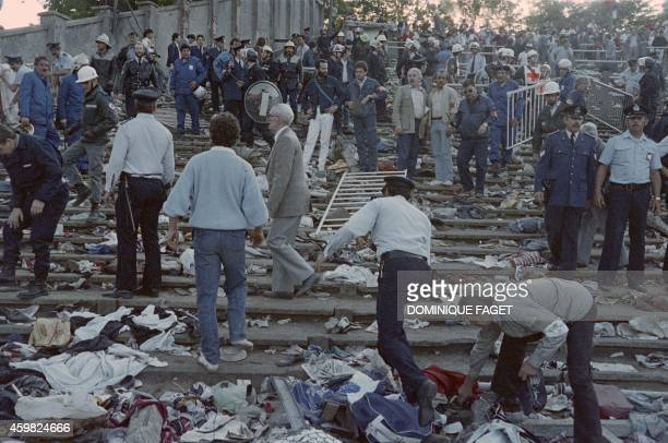 Rescuers and policemen search for victims on May 29 1985 at the scene of riots in Heysel football stadium in Brussels after 39 people lost their...