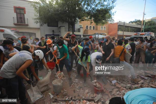 Rescuers and residents look for victims amid the ruins of a building knocked down by a magnitude 71 earthquake that jolted central Mexico damaging...