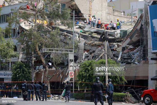Rescuers and residents of Colonia Condesa look for victims amid the ruins of a building knocked down by a magnitude 71 earthquake that jolted central...