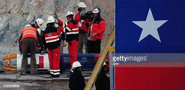Rescuers and technicianscheck the Fenix capsule before starting the rescue operation of the 33 trapped miners at the San Jose mine near the city of...