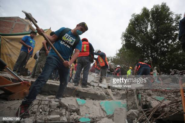 Rescuers and volunteer workers remove rubble from a collapsed building at San Gregorio Atlapulco a day after the magnitude 71 earthquake jolted...