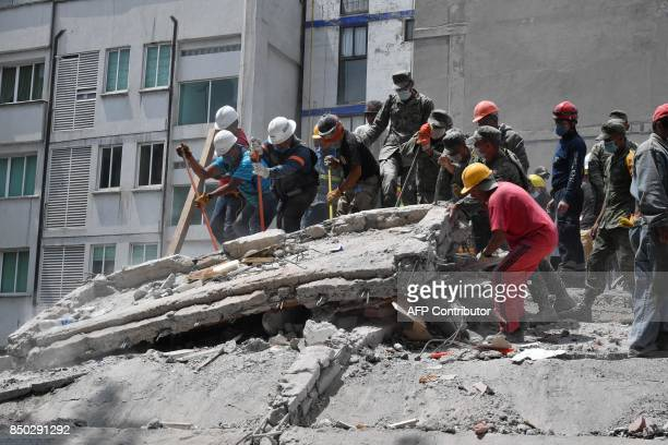 Rescuers and volunteers work clearing from rubble and debris the site where a multistory building was flattened by a 71magnitude quake on the eve...
