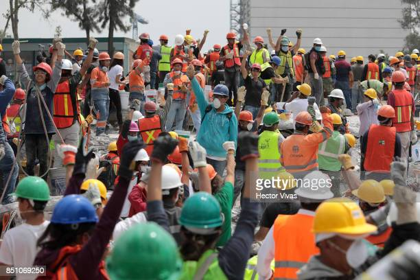 Rescuers and volunteers work in a textile factory that collapsed two days after the magnitude 71 earthquake jolted central Mexico killing more than...