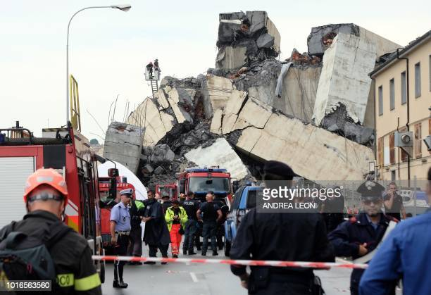 Rescuers are at work amid the rubble of a section of the Morandi motorway bridge that collapsed earlier on August 14 2018 in Genoa Rescuers scouring...