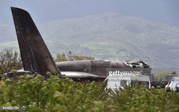 Rescuers are seen around the wreckage of an Algerian army plane which crashed near the Boufarik airbase from where the plane had taken off on April...