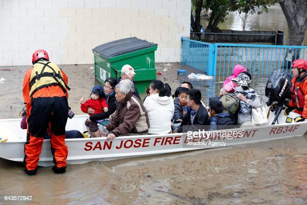 Rescuers are seen in a boat full of people some with babies and pets at a San Jose neighborhood inundated by water from an overflowing creek on...