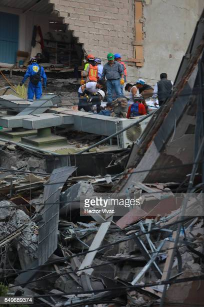 Rescuers assist wounded people in a destroyed building in Colonia Condesa after the magnitude 71 earthquake jolted central Mexico damaging buildings...