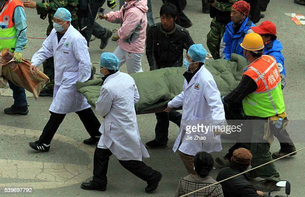 Rescuers carry a 13-year old ethnic tibetan girl, a survivors from debris of destroyed house with her mother in the earthquake-hit town of Gyegu in...