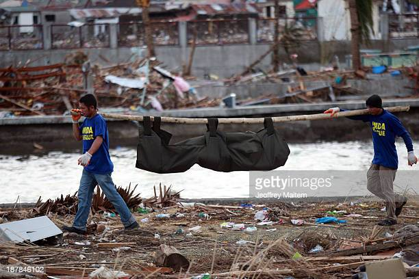 Rescuers carry a body bag containing a dead body in the aftermath of Typhoon Haiyan on November 13 2013 in Tacloban Leyte Philippines Typhoon Haiyan...