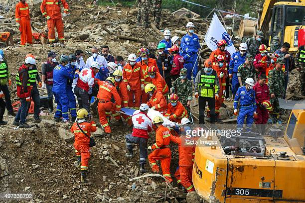 Rescuers carry a body found at the site after a landslide in Lidong village on November 15 2015 in Lishui Zhejiang Province of China A landslide hit...