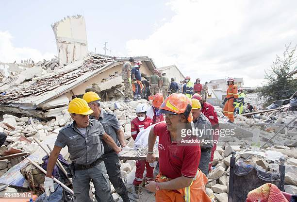 Rescuers carry a body from the rubble after a strong earthquake hit Amatrice on August 24, 2016. Italy was struck by a powerful, 6.2-magnitude...