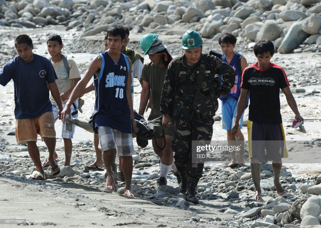 Rescuers carry a dead body retrieved among boulders in the aftermath of Typhoon Bopha in the town of New Bataan, compostela province on December 6, 2012. Nearly 200,000 people are homeless and more than 300 dead after the Philippines suffered its worst typhoon this year, authorities said on December 6, reaching out for international aid to cope with the scale of the disaster.