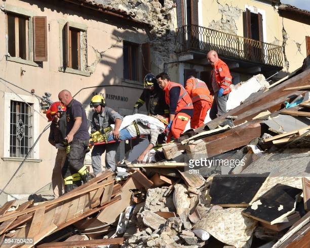 TOPSHOT Rescuers carry a man on a stretcher among damaged buildings after a strong earthquake hit central Italy in Amatrice on August 24 2016 A...