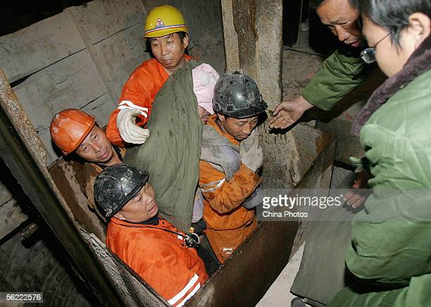 Rescuers carry a miner who has been trapped 11 days underground after a cave-in at Kangli Gypsum Mine at Shangwang Village of Huining Township,...