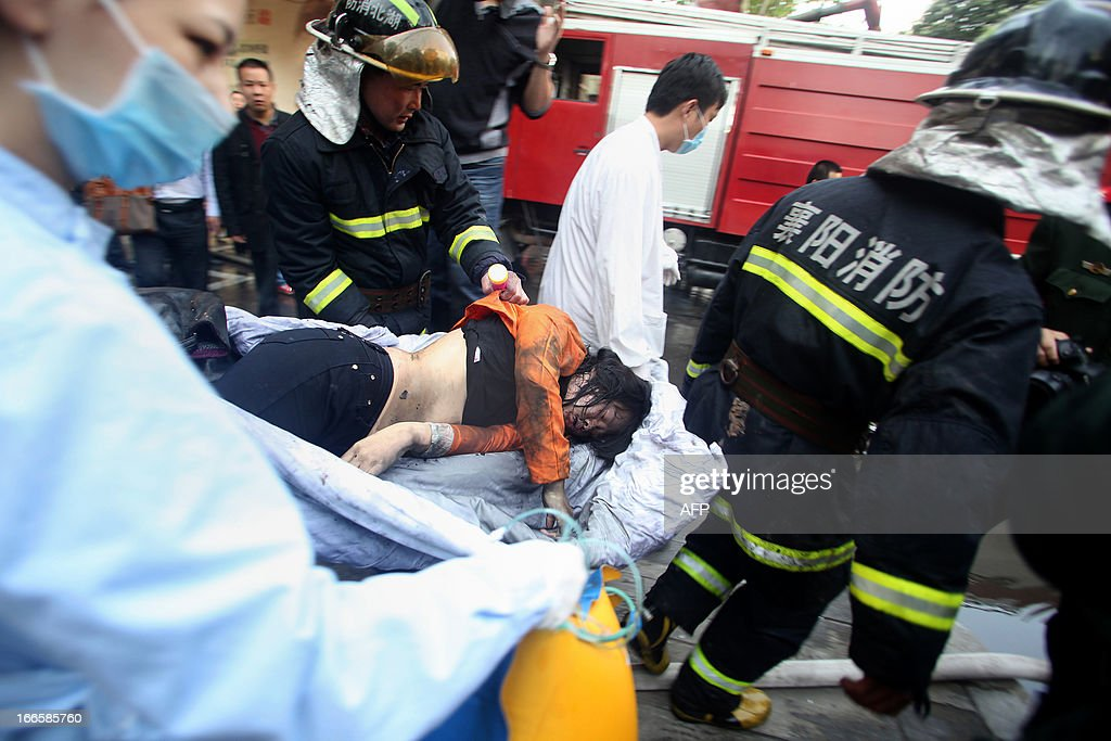 Rescuers carry a survivor from a hotel that caught fire in Xiangyang, central China's Hubei province on April 14, 2013. The fire, started from an Internet cafe downstairs, resulted in 11 deaths and 50 injuries, local government reports annouced. CHINA