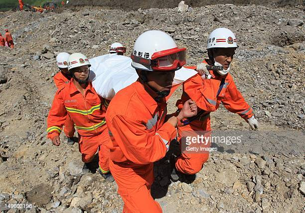 Rescuers carry a victim's body after a mudslide occurred at an iron ore mine on July 31 2012 in Xinyuan China At least 16 people were killed and 12...