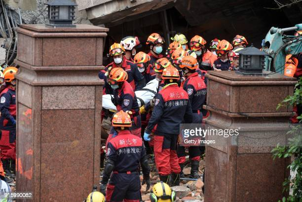 Rescuers carry a victim's body from a damaged building on February 8, 2018 in Hualien, Taiwan. The death toll from the 6.5-magnitude earthquake in...