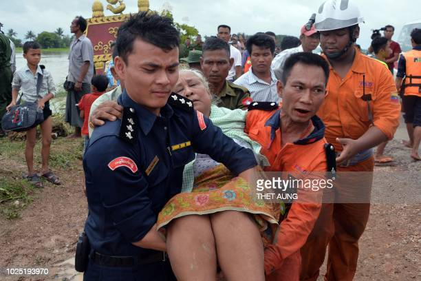 TOPSHOT Rescuers carry an elderly flood victim to safety in Swar township of the Bago region on August 30 2018 Rescuers in boats negotiated muddy...