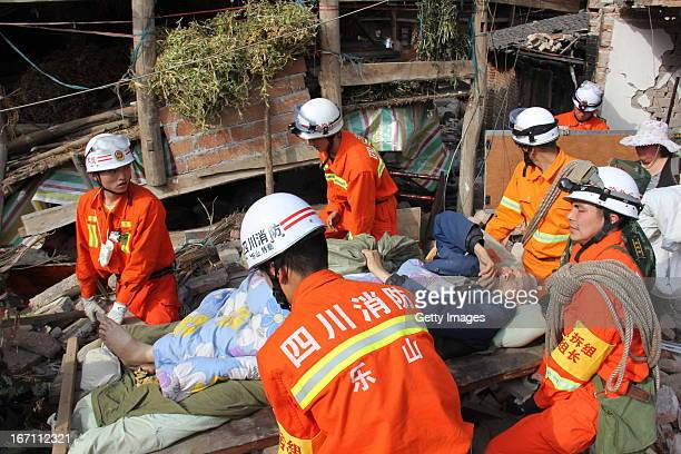 YA'AN CHINA APRIL 20 Rescuers carry an injured person out of a collapsed house after an earthquake struck on April 20 2013 in Lushan County of Ya'an...