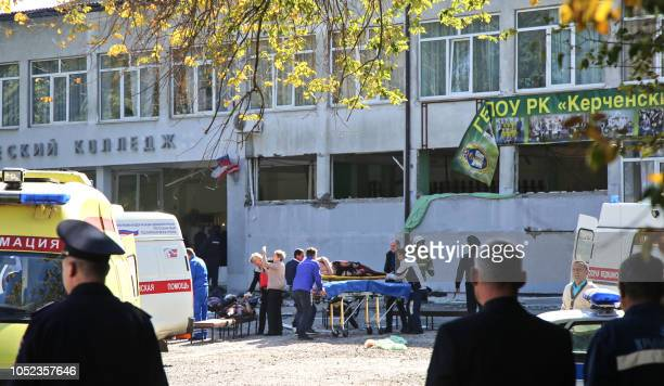 Rescuers carry an injured victim of a blast at at a college in the city of Kerch on October 17 2018 Thirteen people were killed and 50 more wounded...