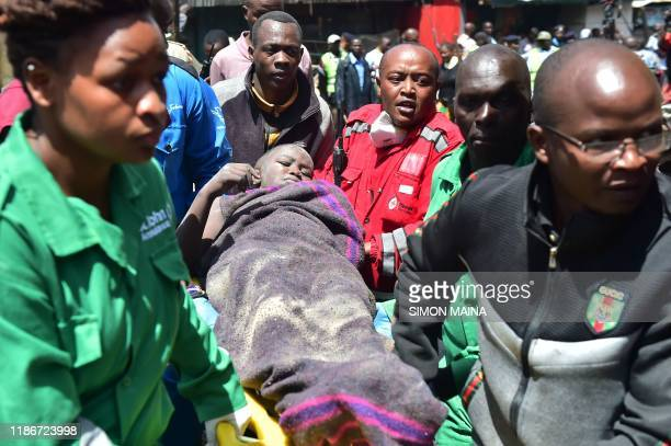Rescuers carry an injured woman out of the scene where a sixstorey building collapsed in Nairobi on December 6 2019