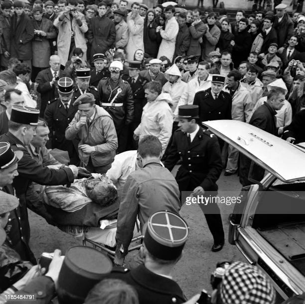 Rescuers carry away American race car driver Walter Hansgen after his FORD GT car left the track on Le Mans circuit, on April 2, 1966 during the...