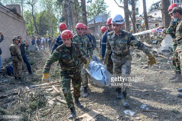 Rescuers carry away the body of a victim at the blast site hit by a rocket during the fighting between Armenia and Azerbaijan over the breakaway...