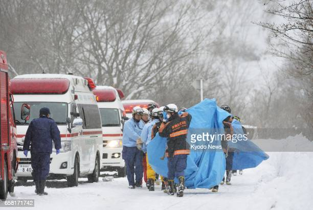 Rescuers carry people injured in an avalanche near a ski slope in Nasu in the eastern Japan prefecture of Tochigi on March 27, 2017. Eight high...