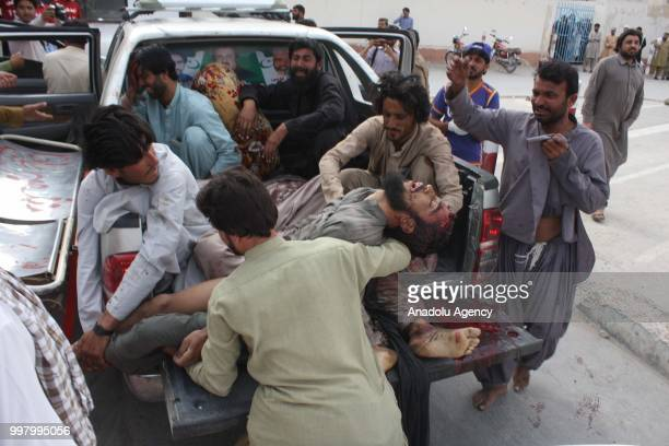 Rescuers carry woundeds to hospital after blasts targeting election rally in Karachi Pakistan on July 13 2018 Workers At least 90 people were killed...