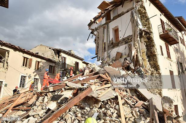 Rescuers clear debris while searching for victims in damaged buildings on August 24, 2016 in Arquata del Tronto, Italy. Central Italy was struck by a...