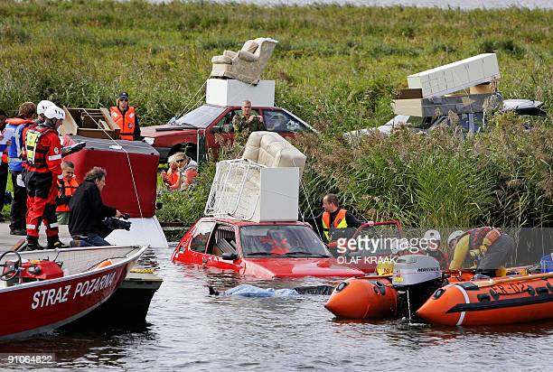 Rescuers come to the aid of drivers who ended up in the water with their car after they fled their houses in a staged rescue operation performed by...