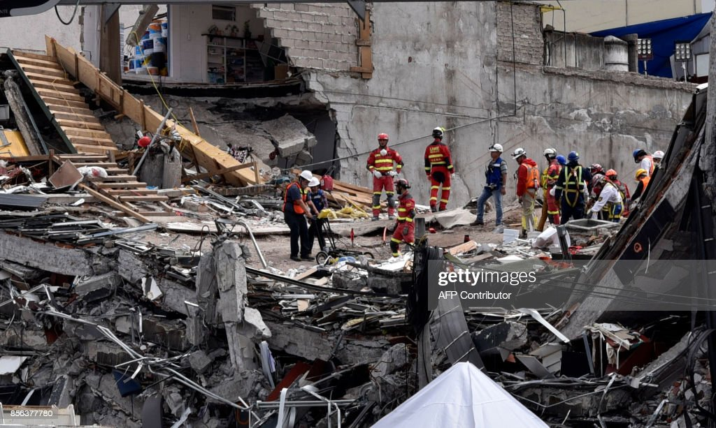 TOPSHOT - Rescuers dig through the rubble looking for victims in one of the buildings crushed during the September 19 earthquake in Mexico City, on October 1, 2017. More than a week after an earthquake that killed over 300 people, a shaken Mexico was torn between trying to get back to normal and keeping up an increasingly hopeless search for survivors. /