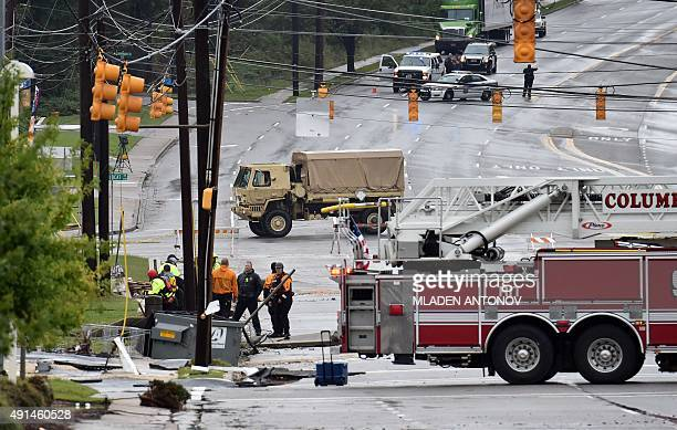 Rescuers discuss at the Garner Ferry road where flash floods destroyed number of businesses in Columbia South Carolina on October 5 2015 Relentless...