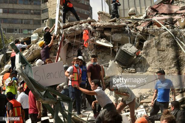 TOPSHOT Rescuers display a placard reading 'Silence' as they hurry to free possible victims out of the rubble of a collapsed building after a quake...