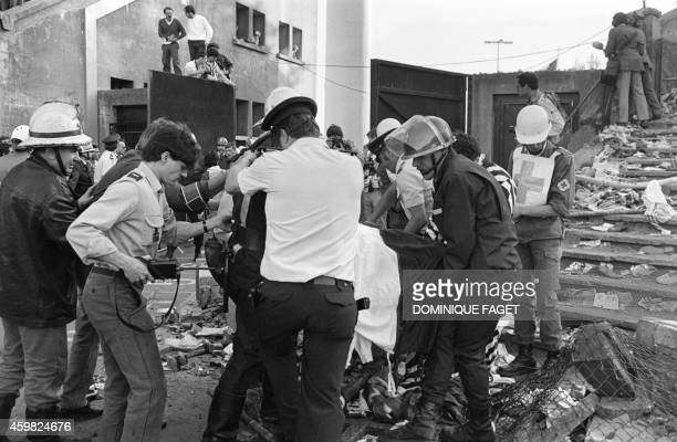 Rescuers evacuate a victim on May 29 1985 at Heysel football stadium in Brussels after 39 people lost their lives in violent incidents one hour...