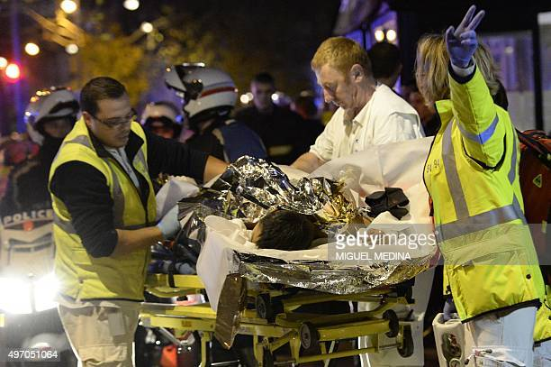 Rescuers evacuate an injured person near the Bataclan concert hall in central Paris, early on November 14, 2015. At least 120 people were killed in a...