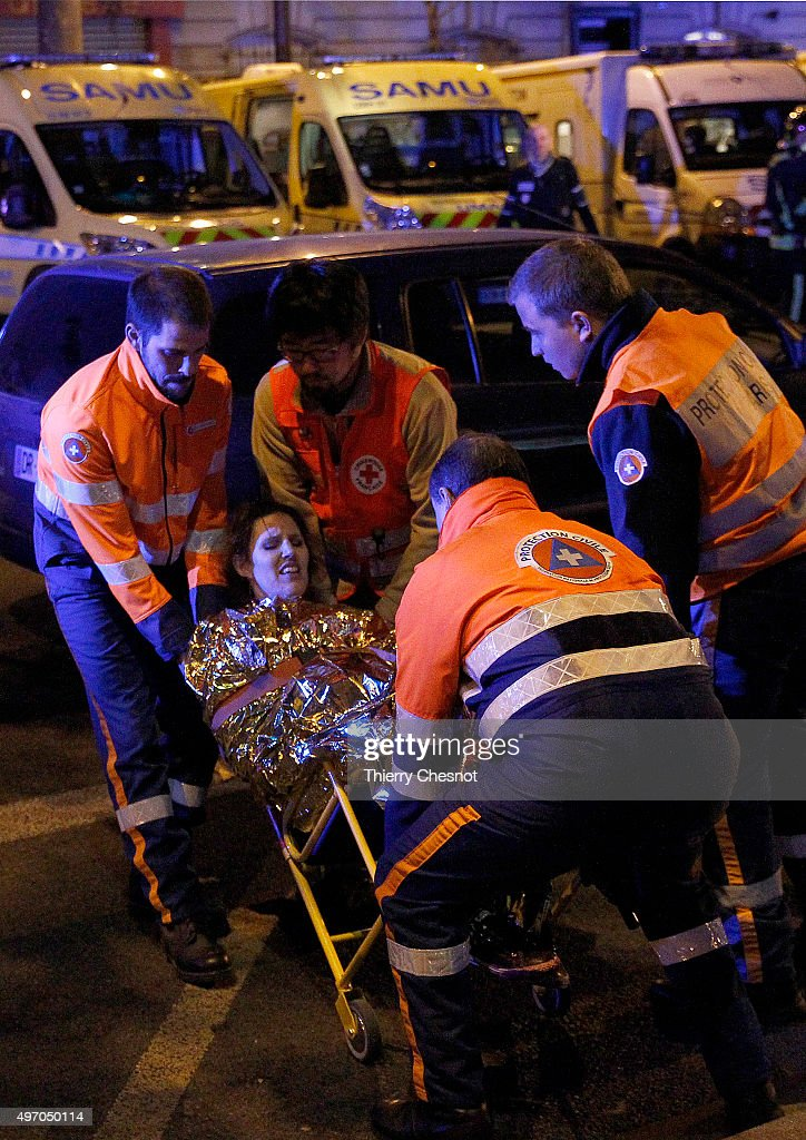 Rescuers evacuate an injured woman on Boulevard des Filles du Calvaire, close to the Bataclan theater, early on November 14, 2015 in Paris, France. According to reports, at least 149 people were killed in a series of bombings and shootings across Paris, including during a soccer game at the Stade de France and a concert at the Bataclan theater.