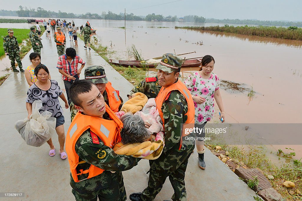 Rescuers evacuate residents from flood-hit areas on July 2, 2013 in Chongqing, China. More than 18,000 people were evacuated after rainstorms hit Tongnan county on Monday and triggered serious flood.