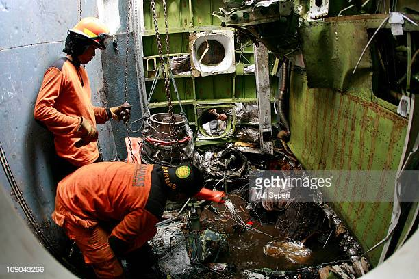 Rescuers examine the wreckage after the SMAC plane type Cessna 212 turbotrop crashed on February 13 2011 in Gunung Kijang Bintan Indonesia Five...